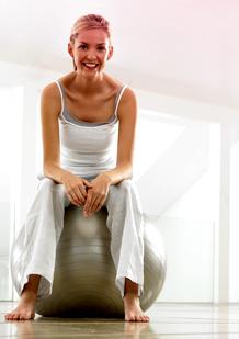 Bilde av en kvinne i treningstøy som sitter på en gymball. Bildet viser, at det er greit å mosjonere og trene når du har menstruasjonen din.