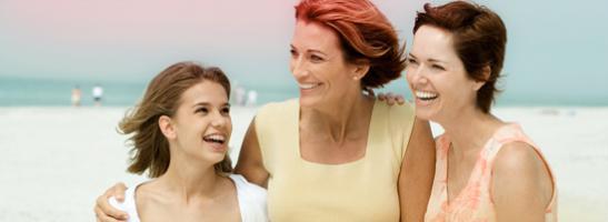 Bilde av 3 kvinner som holder rundt hverandre, en yngre kvinne til venstre og to eldre kvinner til høyre.