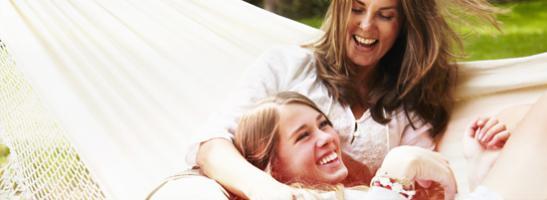 Bilde av to smilende kvinner som ligger i en hengekøye.