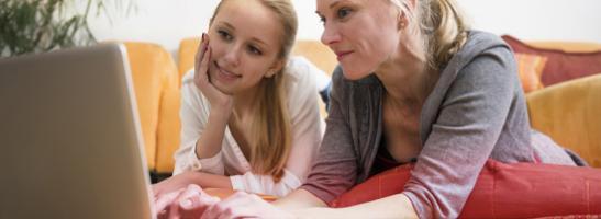 Bilde av mor og datter som bruker en PC sammen. Bildet viser viktigheten av kommunikasjon og å hjelpe datteren din finne den riktige informasjonen.