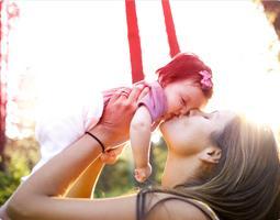 Bilde av en kvinne som kysser og holder en baby.