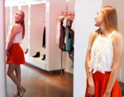Bilde av en jente som står foran speilet og prøver klær.