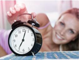 Bilde av en vekkeklokke med en kvinne i bakgrunnen som strekker seg for å slå av vekkeklokka.